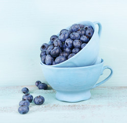 Tasty ripe blueberries in cups, on wooden table
