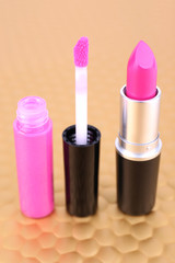 Crimson lipstick and lip gloss on golden background