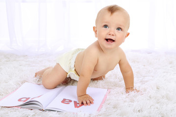 Cute baby boy with book on carpet in room