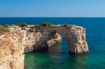 Algarve coast, Portugal. Rocks in the shoreline and blue water