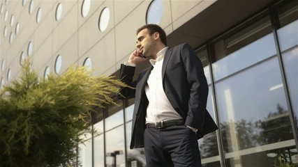 Businessman standing in front of building talking on the phone