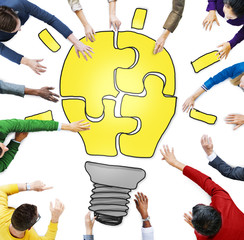 People with Jigsaw Puzzle Forming Light Bulb