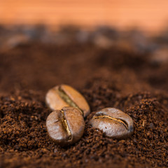 Close-up of coffee beans with roasted coffee heap.