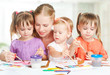 children twin sisters draw paints with mother