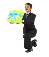 Businessman holding a gift box and kneel down .