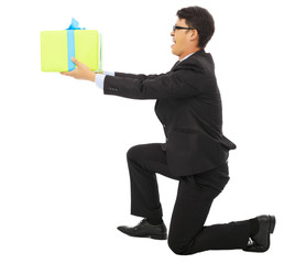 young Business man holding a gift box and kneel.