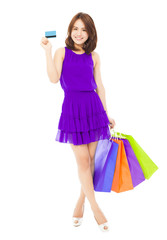 beautiful young woman holding a card and shopping bags.