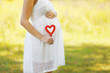 Pregnancy, maternity, family - concept, pregnant woman and heart