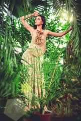 Elegant woman in long evening dress in a forest
