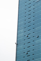 Man climbing on a wall of a tall building in Singapore
