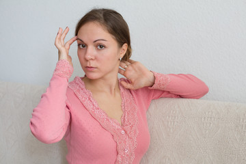 Young woman at home touching her neck and head