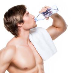 Handsome muscular sportsman drinks water.