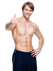 Man with muscular torso shows thumbs up sign.