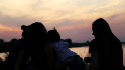 Young mother with baby at the lake at sunset.