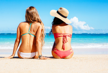 Two Beautiful Girls Sitting on the Beach