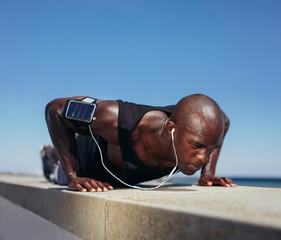 Sporty man doing push-ups outdoors