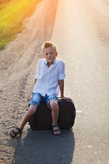 the child sits on a suitcase in the summer sunny day, the travel