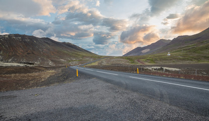 Highway through Iceland volcanic landscape with car at sunset