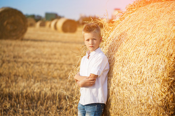 the nice boy in the field of near stack of straw at sunset