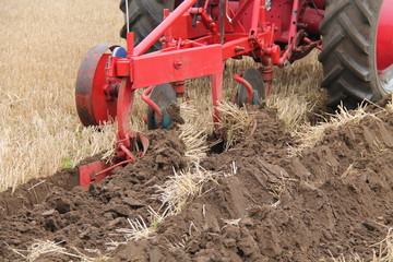A Vintage Plough Cutting a Deep Furrow in a Field.