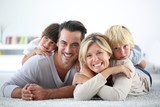 Portrait of happy family laying on carpet - 70507844