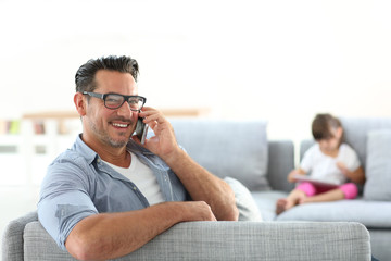 Man in sofa talking on phone, girl in background