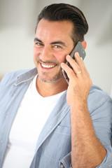 Smiling mature man talking on mobile phone