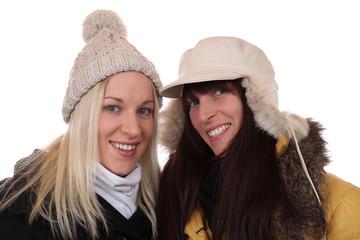 Zwei lachende Frauen im Winter mit Mütze und Schal