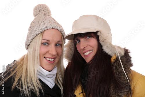canvas print picture Zwei lachende Frauen im Winter mit Mütze und Schal