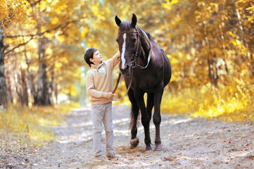 Autumn season happy teenager boy and horse walking in forest