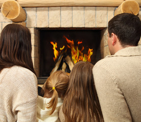 Young happy mother, father and two daughters by a fireplace