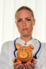 Junge Ärztin mit Sparschwein