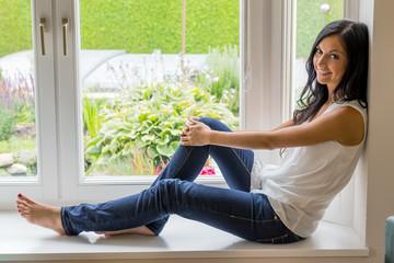 Frau sitzt am Fenster