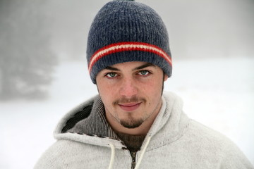 Portrait of a young man in hat in a snowing mountain Spain