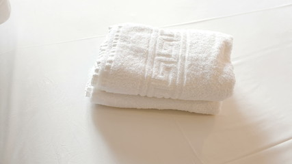 Clean towels with olive branches on bed