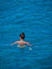 Beautiful girl swimming in blue water