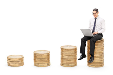 Man working on laptop seated on a stack of coins