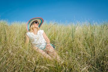 Frau sonnt sich im hohen Gras