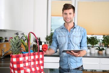 Mann mit einer Einkaufstasche voller gesunder Lebensmittel