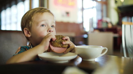 Little boy eating sandwich in a cafe
