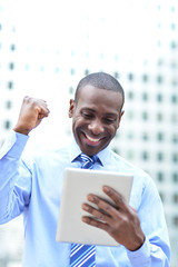 Executive celebrates his success holding a tablet