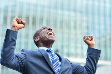 Excited businessman raising his arms