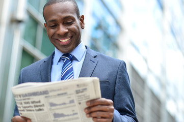 Handsome african man reading a newspaper