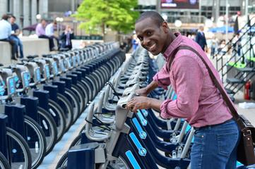 Smiling man parking his bicycle