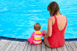 mother and daughter sitting on the pool