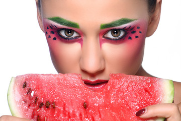 Beautiful young woman eating watermelon