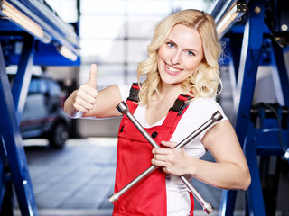 Female apprentice in a garage shows thumb up