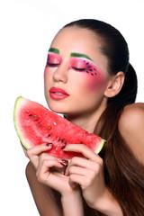 Beautiful young woman eating watermelon