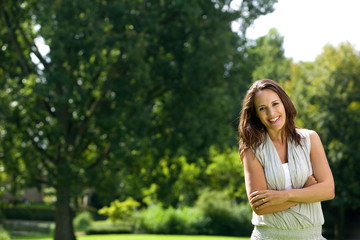 Smiling woman standing outdoors with arms crossed