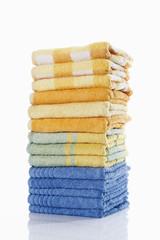 Stapel von mehreren farbigen Handtücher vor weißem Hintergrund